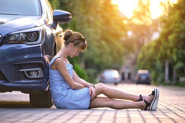 Junge fahrerin sitzt neben ihrem kaputten auto und wartet auf hilfe. konzept für fahrzeugprobleme.