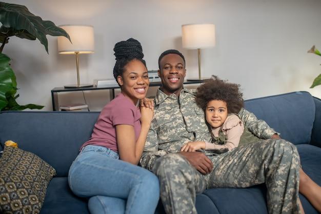 Junge familie. afroamerikanischer kleiner lächelnder mädchenmann in militäruniform und frau mit frisur, die zu hause zusammen auf dem sofa sitzt