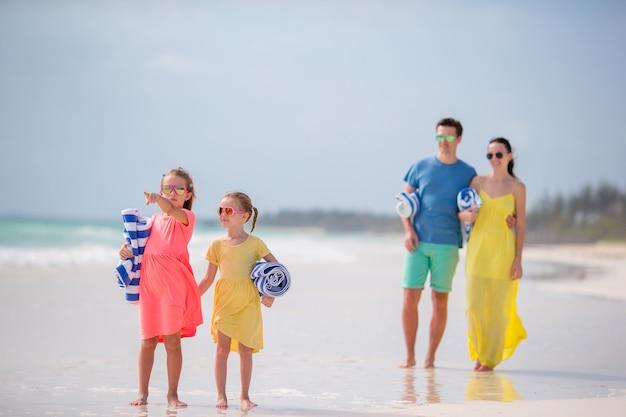 Junge familie am strand. kleine kinder mit handtüchern