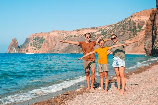 Junge familie am weißen strand während der sommerferien