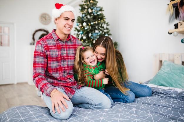 Junge familie auf dem bett zu weihnachten