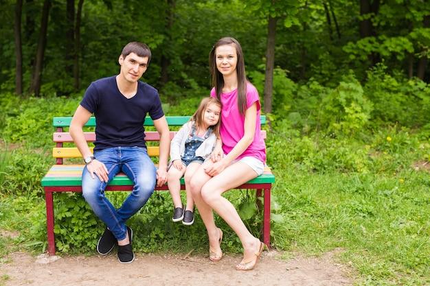 Junge familie, die auf einer bank im sommerpark sitzt.