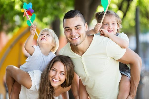 Junge familie, die bunte windmühlen mit kindern spielt