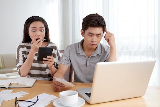 Junge familie, die die routine der familienbuchhaltung durch die höhe der ausgaben betont