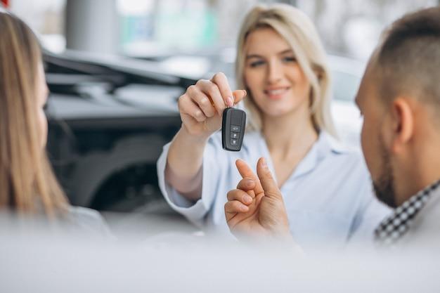 Junge familie, die ein auto an einem händler kauft