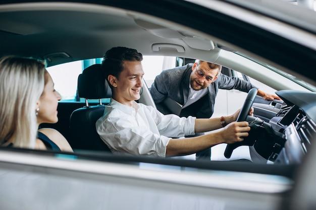 Junge familie, die ein auto in einem autosalon kauft