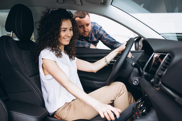 Junge familie, die ein auto in einem autosalon wählt