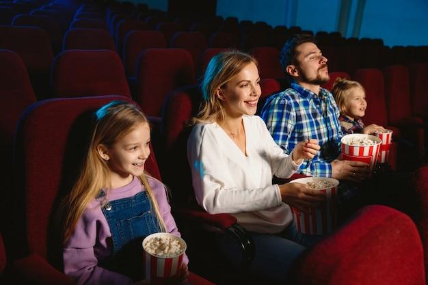 Junge familie, die einen film in einem kino sieht