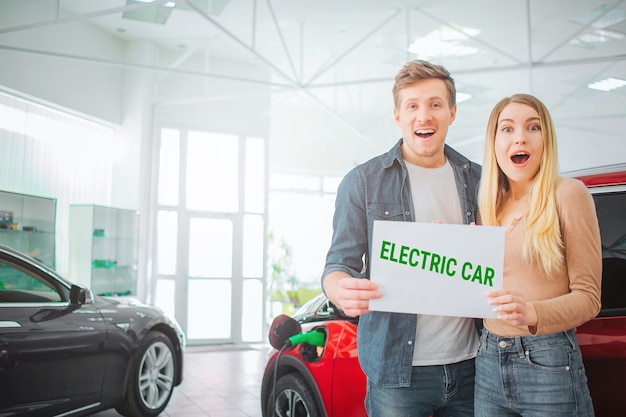 Junge familie, die erstes elektroauto im ausstellungsraum kauft. freudiges attraktives paar, das papier mit wort elektroauto hält, während in der nähe von öko-rotfahrzeug steht. elektroautoverkauf im autosalon