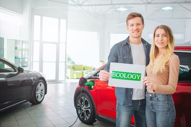 Junge familie, die erstes elektroauto im ausstellungsraum kauft. lächelndes attraktives paar, das papier mit grünem wort ökologie hält, während nahe elektrofahrzeug steht. umweltfreundliches auto schützt eine ökologie.