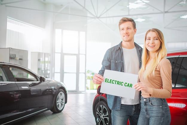 Junge familie, die erstes elektroauto im ausstellungsraum kauft. lächelndes attraktives paar, das papier mit wort elektroauto hält, während in der nähe von öko-rotfahrzeug steht. elektroautoverkauf im autosalon