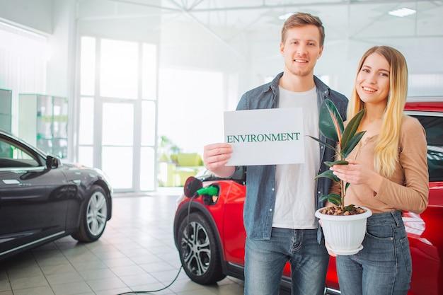 Junge familie, die erstes elektroauto im ausstellungsraum kauft. lächelndes attraktives paar, das papier mit wort umwelt und blumentopf hält, während in der nähe von öko-rot-fahrzeug steht. grünes autokonzept