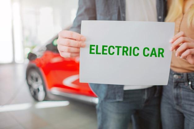 Junge familie, die erstes elektroauto im ausstellungsraum kauft. nahaufnahme der hände, die papier mit wort elektroauto halten. elektroauto mit öko-batterie für umweltschutz.