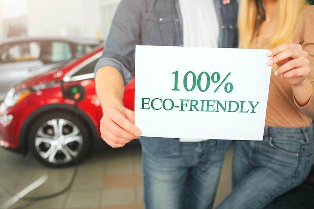 Junge familie, die erstes elektroauto im ausstellungsraum kauft. öko-auto. nahaufnahme der hände, die papier mit wort umweltfreundlich auf batterie-elektroautohintergrund halten. öko-technologie in der automobilindustrie