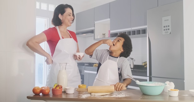Junge familie, die essen in der küche kocht glückliches kleines mädchen mit ihrer mutter, die teig mischt