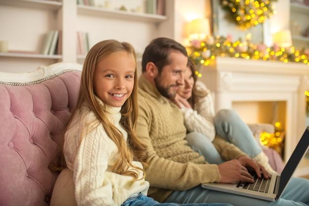 Junge familie, die etwas auf einem laptop beobachtet