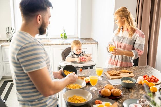 Junge familie, die frühstück mit baby genießt