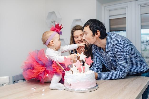 Junge familie, die geburtstag mit einem kuchen feiert