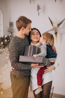 Junge familie, die geschenke mit kleinem sohn auf weihnachten auspackt