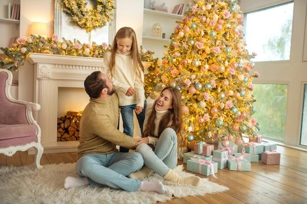Junge familie, die glücklich sitzt, nahe dem neujahrsbaum zu sitzen