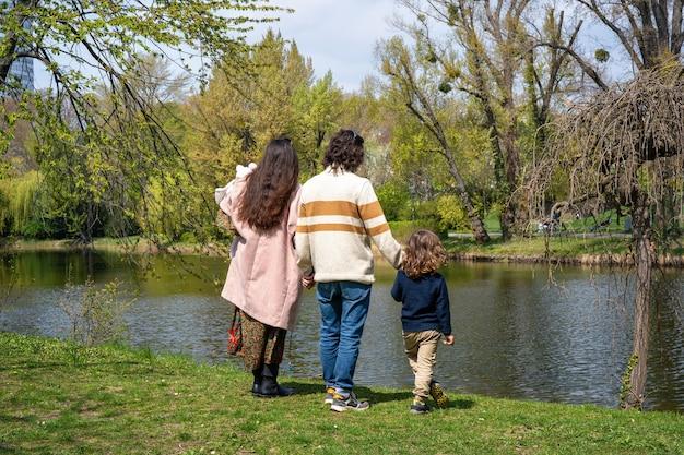Junge familie, die in einem park bleibt und händchen hält, dreht sich mit dem rücken in die kamera