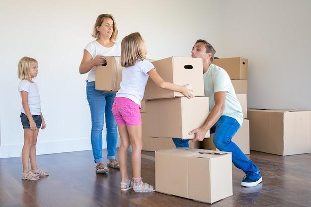 Junge familie, die kisten in neues haus oder wohnung trägt