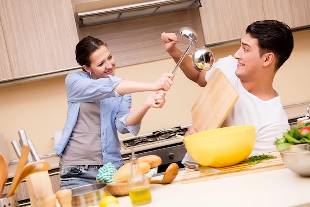 Junge familie, die lustigen kampf an der küche tut
