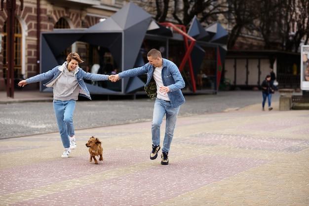 Junge familie, die mit einem hund durch die straßen der stadt geht
