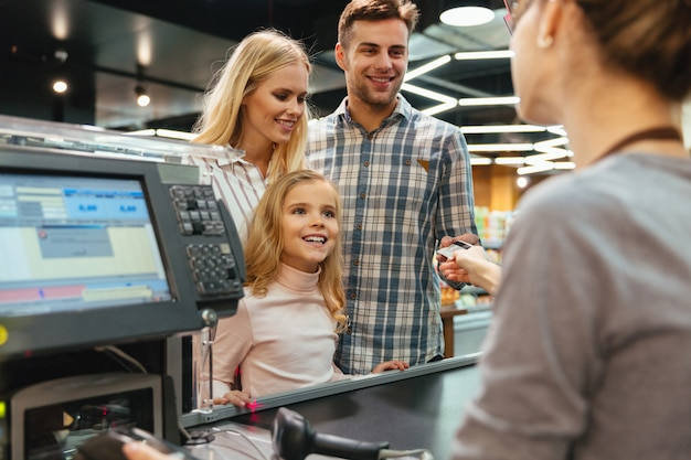 Junge familie, die mit einer kreditkarte zahlt