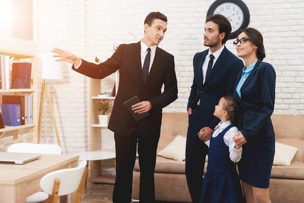 Junge familie, die neues haus mit grundstücksmakler bespricht.