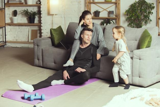 Junge familie, die sich nach dem training zu hause ausruht
