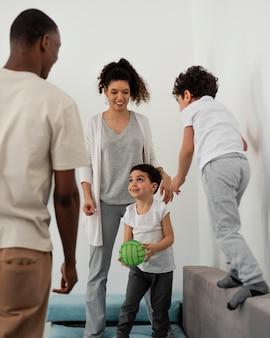 Junge familie, die spaß beim spielen mit ball hat