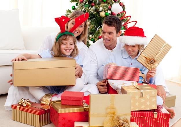 Junge familie, die spaß mit weihnachtsgeschenken hat