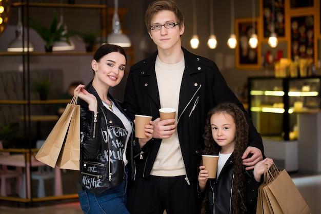 Junge familie, die zeit in einem café nach dem einkaufen hat mama papa kleine tochter tee und café trinken