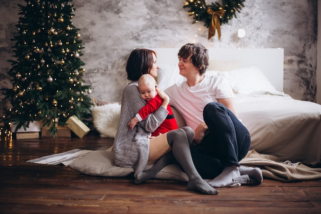 Junge familie, die zu hause über weihnachtsbaum umarmt