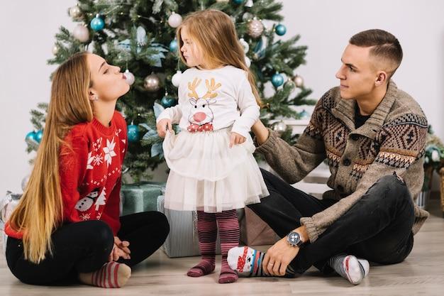 Junge familie, die zu hause weihnachten feiert
