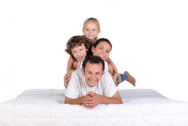 Junge familie, die zusammen auf der matratze und der aufstellung liegt.