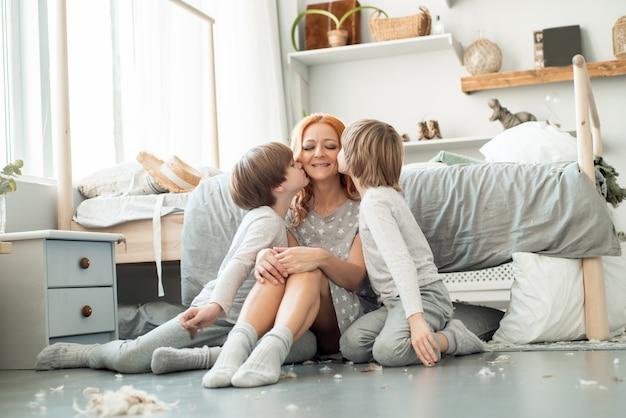 Junge familie, die zusammen im bett der eltern stillsteht