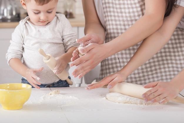 Junge familie, die zusammen kocht. ehemann, ehefrau und ihr kleines baby in der küche. familie, die den teig mit mehl knetet. die leute kochen das abendessen oder frühstück.