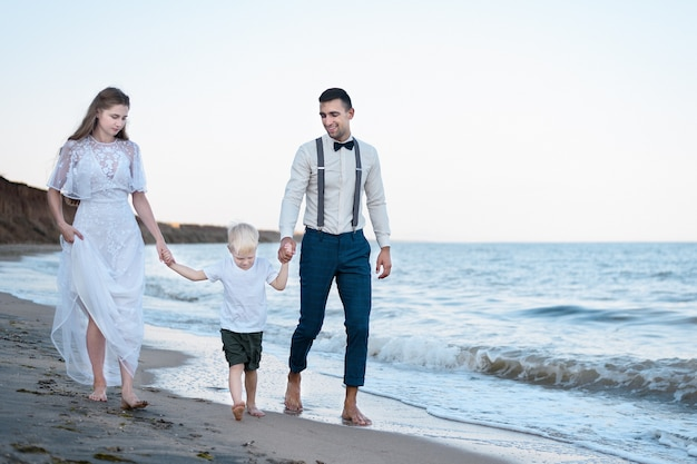 Junge familie geht mit einem kleinen kind am strand spazieren