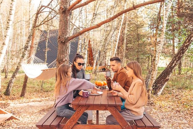 Junge familie im herbsttag auf picknick. familiencamping