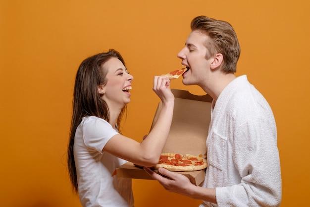 Junge familie in der hauskleidung auf gelbem orange in der quarantäne mit italienischen pizza-peperoni füttern einander gute familienbeziehungen lustiges familienkonzept