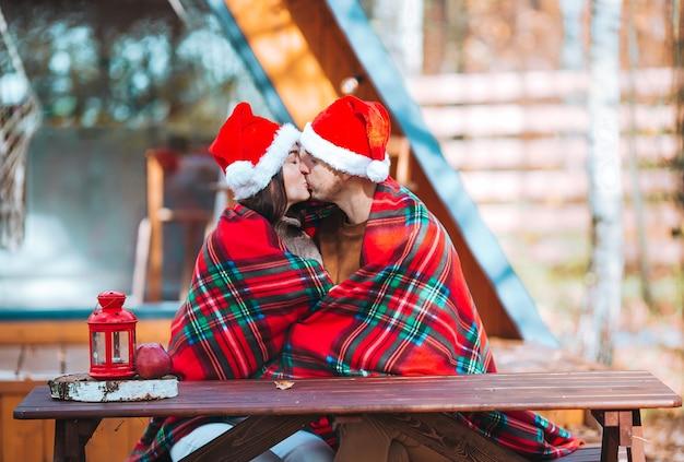 Junge familie in der weihnachtsmütze, die auf dem hölzernen alten tischhintergrund ihres hauses sitzt