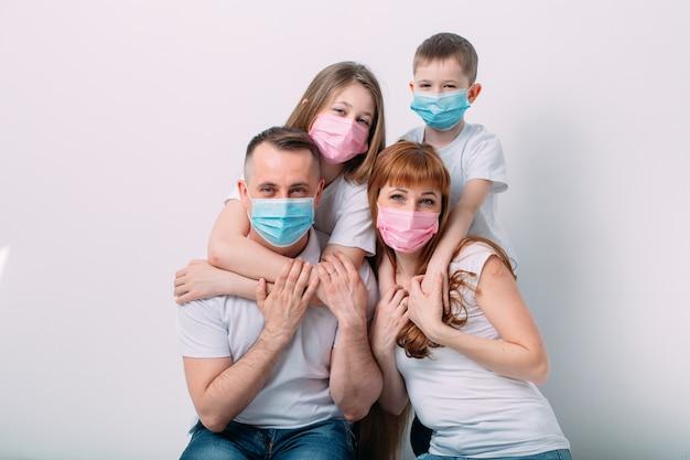 Junge familie in medizinischen masken während der quarantäne zu hause.