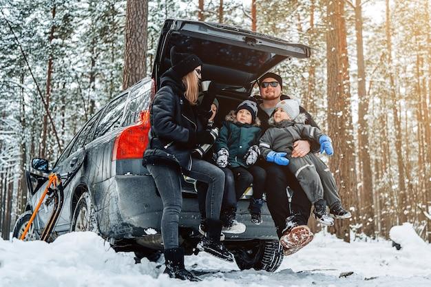 Junge familie in warmer kleidung posiert vor der kamera, die tagsüber auf dem kofferraum des autos im winterwald sitzt.