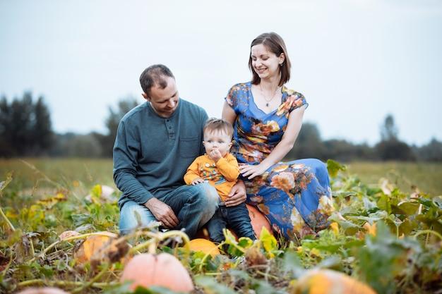 Junge familie, mama, papa und kleiner junge verbringen zeit auf der kürbisfarm