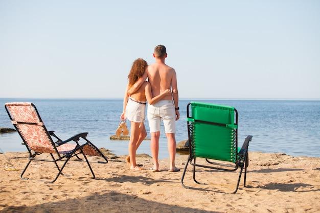Junge familie, mann und frau entspannen sich auf dem ozean.