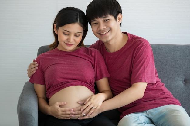 Junge familie mann und frau sitzen auf einer couch. sie lächeln und schauen in eine kamera. ein mann und eine schwangere frau berühren einen bauch. erwarte ein gesundes baby.