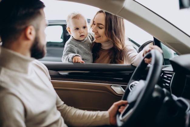 Junge familie mit baby, die ein auto wählt