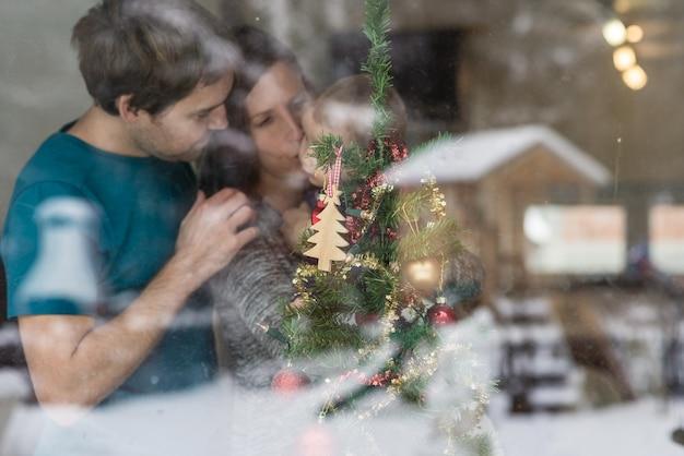 Junge familie mit baby hinter geschmücktem weihnachtsbaum zu hause durch ein glasfenster gesehen.